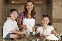 Familia en cocina que cocina y que cuece al horno Imagen de archivo libre de regalías