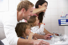 Familia en dientes de cepillado del cuarto de baño Fotos de archivo