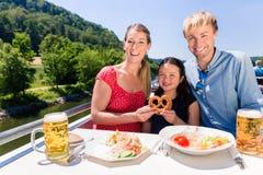 Familia en el almuerzo en travesía del río con los vidrios de cerveza en cubierta fotos de archivo