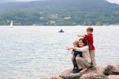 Familia en el banco del lago Fotografía de archivo libre de regalías