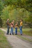 Familia en el bosque del otoño que mira detrás Foto de archivo