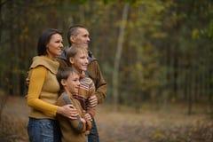 Familia en el bosque del otoño que mira lejos Imágenes de archivo libres de regalías