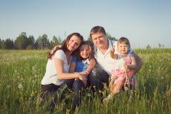 Familia en el campo verde Fotos de archivo