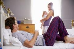 Familia en el dormitorio que detiene a la hija recién nacida del bebé fotografía de archivo