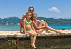 Familia en el embarcadero de madera en el mar foto de archivo