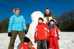 Familia en el invierno que se coloca delante de su snowma Fotos de archivo libres de regalías