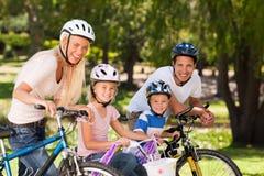 Familia en el parque con sus bicis Foto de archivo libre de regalías