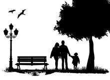 Familia en el parque de la ciudad Foto de archivo libre de regalías