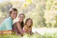 Familia en el parque que tiene una comida campestre y una sonrisa Imagenes de archivo