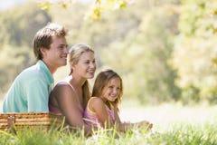 Familia en el parque que tiene una comida campestre y una sonrisa Imagen de archivo libre de regalías