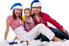 Familia en el sombrero de Santa que se sienta en nieve artificial Fotografía de archivo