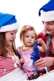 Familia en el sombrero de Santa que se sienta en nieve artificial Fotografía de archivo libre de regalías