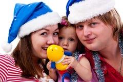 Familia en el sombrero de Santa que se sienta en nieve artificial Imágenes de archivo libres de regalías