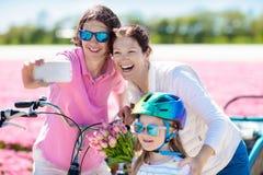 Familia en la bici en campos de flor del tulip?n, Holanda foto de archivo libre de regalías