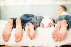 Familia en la cama en casa con su mostrar de los pies Fotos de archivo