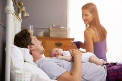 Familia en la cama que detiene a la hija recién nacida durmiente del bebé imagenes de archivo