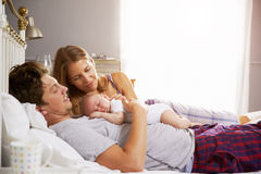 Familia en la cama que detiene a la hija recién nacida durmiente del bebé fotografía de archivo