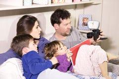 Familia en la cama que toma el selfie con la cámara Foto de archivo libre de regalías