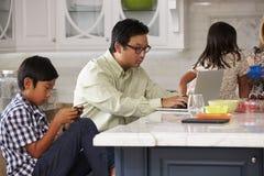 Familia en la cocina que desayuna y que usa los dispositivos de Digitaces Foto de archivo