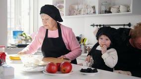 Familia en la cocina que hace los postres Una mujer mayor alrededor para cortar el plátano metrajes