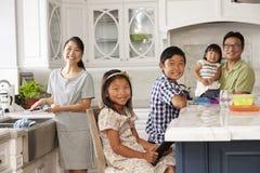 Familia en la cocina que hace tareas y que usa los dispositivos de Digitaces Foto de archivo libre de regalías
