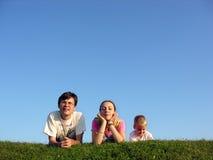 Familia en la hierba bajo el cielo 2 Imagen de archivo