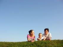 Familia en la hierba bajo el cielo foto de archivo