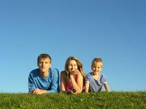 Familia en la hierba bajo el cielo azul Fotos de archivo libres de regalías