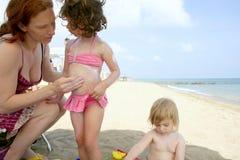 Familia en la humedad de la pantalla de sol de la playa Imágenes de archivo libres de regalías
