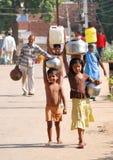 Familia en la India, que debe llevar el agua para contener Fotos de archivo