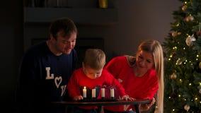 Familia en la Navidad que se sienta debajo del árbol que mira como el niño sopla hacia fuera las velas y las risas Risa de la mam almacen de metraje de vídeo