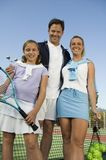 Familia en la opinión de ángulo bajo neta del retrato del campo de tenis que hace una pausa imágenes de archivo libres de regalías