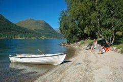Familia en la orilla del lago que tiene comida campestre Foto de archivo