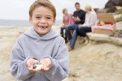 Familia en la playa con la sonrisa de la comida campestre y del muchacho Foto de archivo libre de regalías