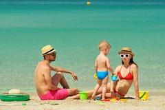 Familia en la playa Niño que juega con la madre y el padre Foto de archivo