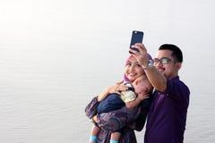 Familia en la playa que hace un autorretrato con un teléfono móvil Foto de archivo