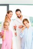 Familia en la rutina del cuidado dental en cuarto de baño Fotos de archivo libres de regalías