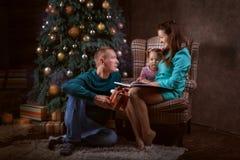 Familia en la sala de estar por el árbol de navidad Fotos de archivo libres de regalías