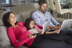Familia en la tableta de Sofa With Laptop And Digital que ve la TV fotos de archivo libres de regalías