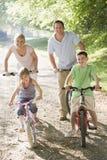 Familia en las bicis en la sonrisa del camino Imágenes de archivo libres de regalías