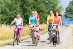 Familia en las bicis en la trayectoria de la suciedad Foto de archivo