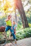 Familia en las bicis madre e hijo que montan una bicicleta junto al aire libre fotos de archivo