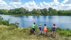 Familia en las bicis que completan un ciclo al aire libre, los padres y los niños activos en las bicicletas, opinión aérea la fam foto de archivo