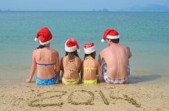 Familia en los sombreros de santa que se divierten en la playa Imágenes de archivo libres de regalías
