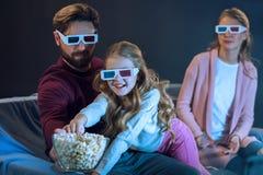 Familia en los vidrios 3d que mira película y que come las palomitas Foto de archivo