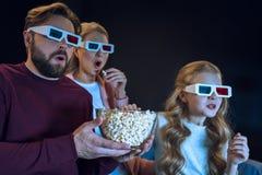 Familia en los vidrios 3d que mira película y que come las palomitas Imagen de archivo