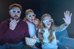 Familia en los vidrios 3d que mira película y que come las palomitas Fotografía de archivo libre de regalías