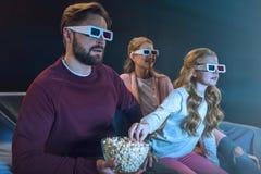 Familia en los vidrios 3d que mira película y que come las palomitas Foto de archivo libre de regalías