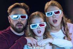 Familia en los vidrios 3d que mira película y que come las palomitas del cuenco Imagen de archivo libre de regalías