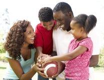 Familia en parque con fútbol americano imagen de archivo